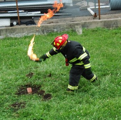 Photo of a firefighter starting a fire to simulate arson